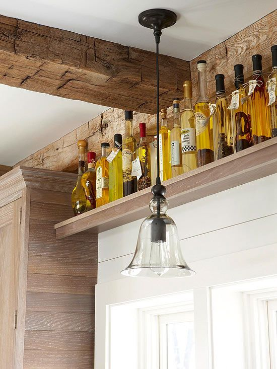 A single ledge or shelf installed near the ceiling can take advantage of untapped storage potential. This long shelf displays and stores bottles of oils and vinegars, showing off golden hues and shapely outlines while drawing attention to the rustic ceiling beams and beautiful lighting./