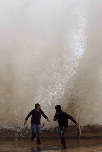 Homens libaneses correm de onda em calçada à beira-mar na cidade de Sidon.