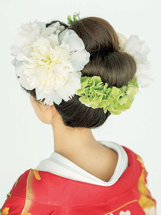 トップと両サイドにふくらみをもたせて留め、後ろは3 つに分けてそれぞれすき毛を入れてシニヨンに。ヘッドコサージュをたっぷりと飾って豪華な衣装に...