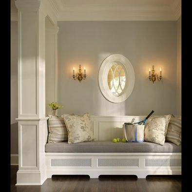 Bench seating underneath oval window...love the soft colors & the two wall sconces