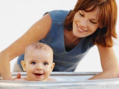 Eine Mutter badet ihr Baby.