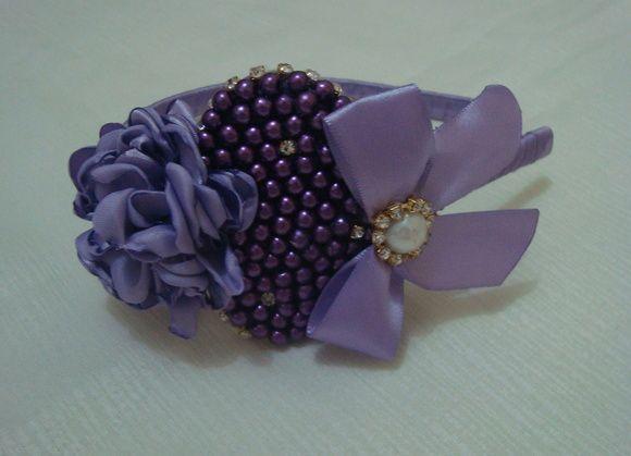 Tiara encapada em fita cetim lilás com flor em cetim, coração em pérola e laço com meia pérola e strass. Uma linda tiara para uma linda princesa. R$ 19,90