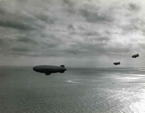 A trio of US Navy airships on convoy duty patrols above seemingly placid Atlantic waters.