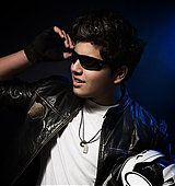 Portrait of handsome stylish teen boy posing in the studio over dark blue background, wearing bikers outfit and - Stock Photo