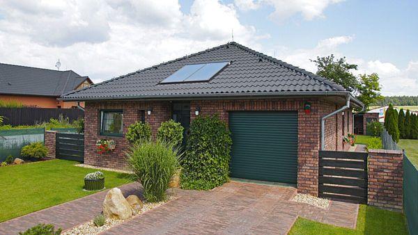Obklad z režných cihelných pásků, zelená okna, pečlivě udržovaná zahrada a jezírko vytvářejí klidnou atmosféru domova v náručí přírody.