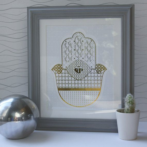 A Hamsa is an art piece that in Jewish mysticism is said to bring luck and ward against the evil eye. In this Hamsa Wall Art your eye is drawn to the illustrative Chai in the center of the design. The Gold Foil Chamsa has ornate details highlighted throughout the design is the Jewish