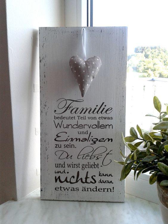 """Weißes Holzschild mit der Beschriftung """"Familie bedeutet, Teil von etwas Wundervollem und Einmaligem zu sein. Du liebst und wirst geliebt und nichts kann daran etwas ändern.""""  Es ist ein schönes...:"""