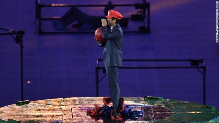 Japanese Prime Minister Shinzo Abe, dressed as Super Mario, holds a red ball…