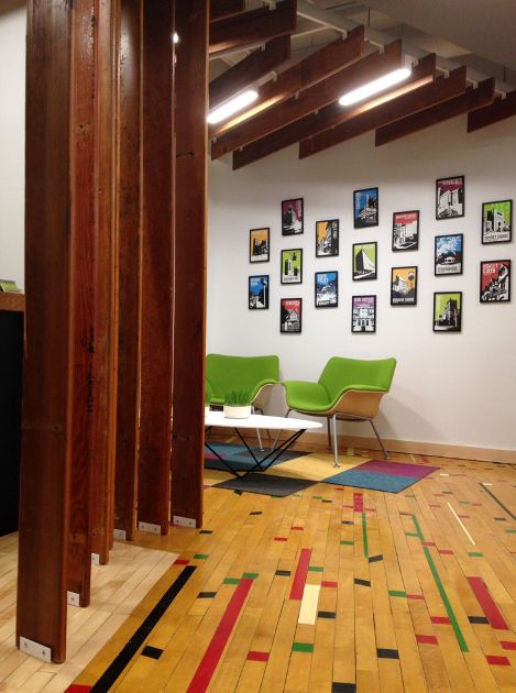 Original gym flooring and reclaimed bleacher boards add character to the Ashley McGraw office in Syracuse NY.