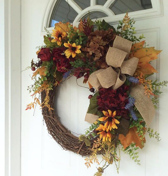 This cheery farmhouse wreath is a lovely mixture of color that is perfect for the upcoming months. A natural, rustic grapevine wreath is covered with hydrangeas, dahlias, lavender and black-eyed Susans. Seeded eucalyptus, golden yellow maple leaves, garden ferns and other foliages make the design look natural and garden-like. Deep burgundy berries are tucked amongst the foliage, adding the perfect touch to this rustic summer design. A bow of wired burlap ribbon completes the look…