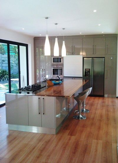 This High Gloss *Melamine Impact (*Imported) kitchen in Niemann Graubraun features: Tops: 30mm Rustenburg Granite and Solid Kiaat, Door Profile: Square Line, Handles: Roman Bar Handles, Special Features: Aluminium roller shutter, Admiral Graphite sink, ML mixer and s/steel kickplates.