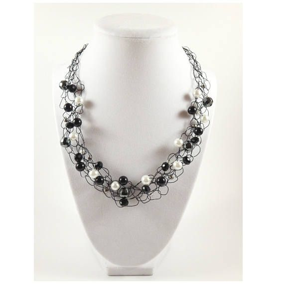 Give your outfit a bold yet classic look with this black statement necklace! Designed with the fashionable, modern woman in mind, this crochet necklace is a delicate weave of black wire with black, white and grey beads. It's the perfect accessory to dress up a casual outfit or to add to an evening outfit to complete your look!