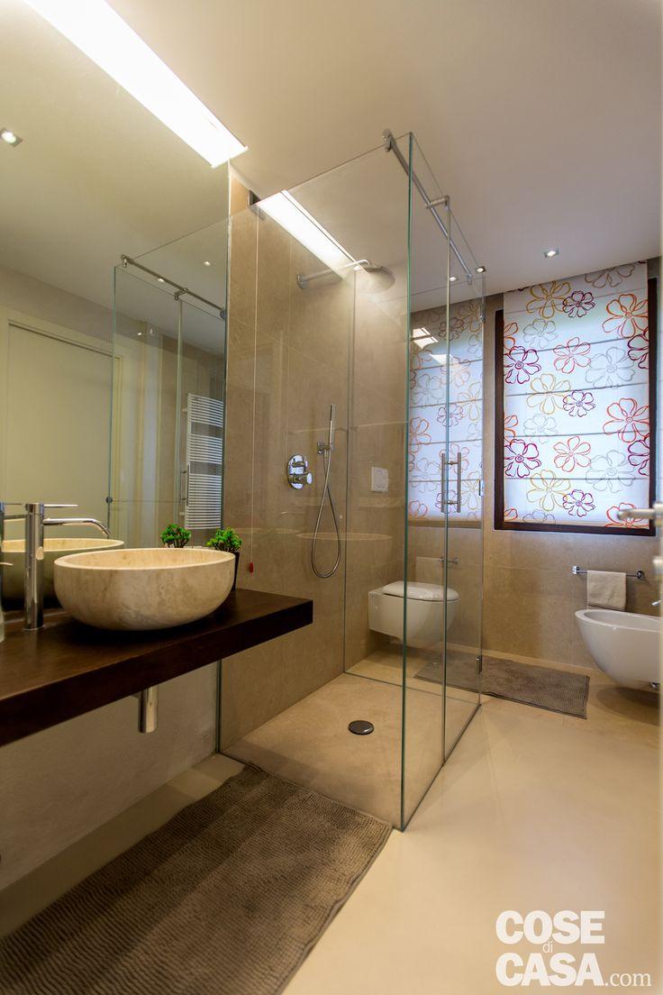 Dalla parete di fronte al letto matrimoniale si accede, attraverso una porta scorrevole interna, nel bagno. Il lavabo poggia su consolle di legno e il box doccia ha piatto a filo pavimento.