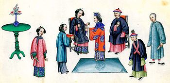 """A Qing Dynasty wedding. The groom's parents are seated. The bride is the one in the centre wearing a red dress and blue headpiece, presenting tea to her mother-in-law. The groom usually wears a sash forming an """"X"""" in front of him. Sometimes the """"X"""" includes a giant bow or flower, though not in this picture."""