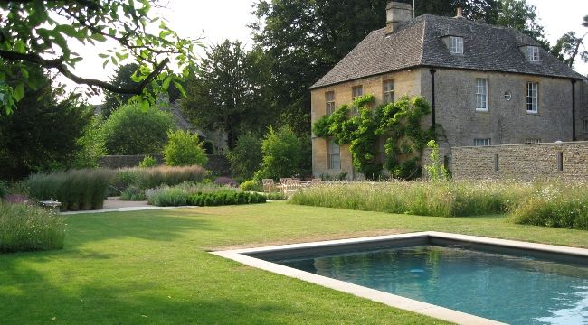 Dan Pearson, designed this garden for an old Georgian rectory which is tucked away in the heart of the Cotswolds.Variations of stone were used throughout to create a stylish and understated feel to the garden. New terraces and paths were constructed using sawn stone paving. Dry stone walls were created using a combination of reclaimed and local quarried stone for a sympathetic build style.