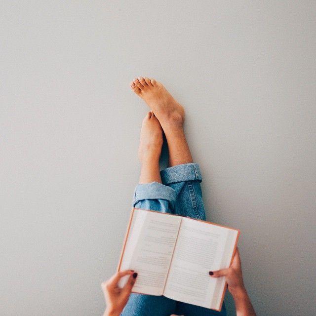 Pés na parede com um livro