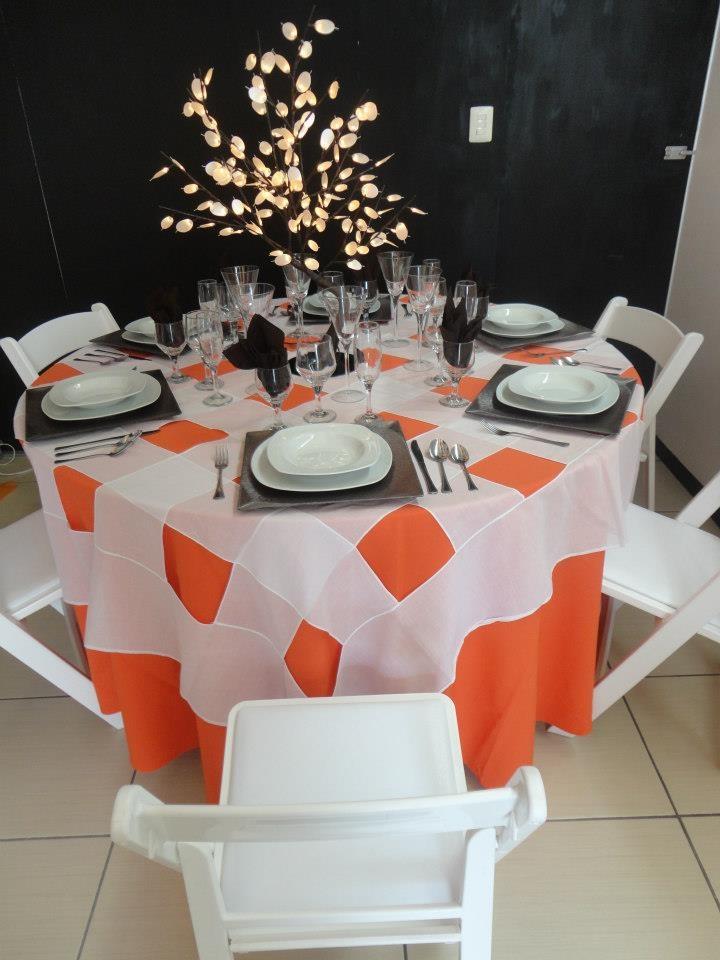 Mesa redonda con mantel color naranja y cubremantel blanco a cuadros. Silla Avant Garde.