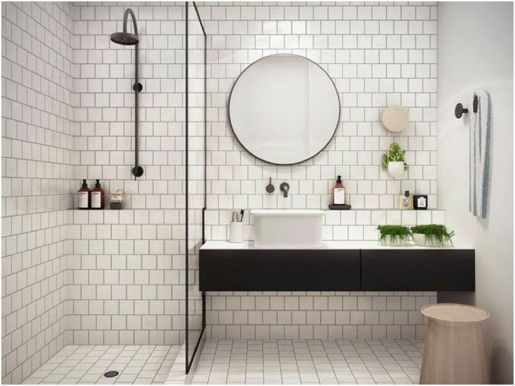 White tiles black grout, lip above the sink also in shower tiled in, round mirror.