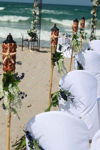 Tiki torches as aisle decor for beach wedding