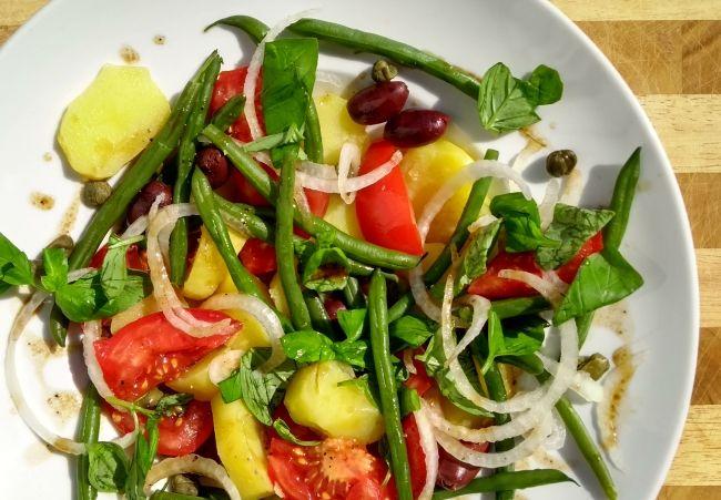 Veganer Nizza-Salat  Für 4 Portionen: 6 große Kartoffeln, festkochend 350 g grüne Bohnen 6 reife Tomaten ½ Gemüsezwiebel 2 EL Kapern 1-2 Handvoll schwarze Oliven 2 EL Weißweinessig oder weißer Balsamico-Essig 6 EL Olivenöl Salz Pfeffer 1 Handvoll Basilikumblätter