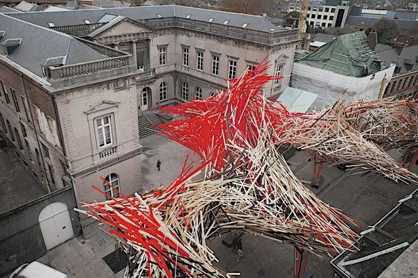 A 141-Foot Wave of Crashing Lumber Guards the Grand Place in Mons  ||  The wild installation stands in stark contrast to the buildings of Belgium's historic Rue de Nimy. https://www.atlasobscura.com/places/the-passenger