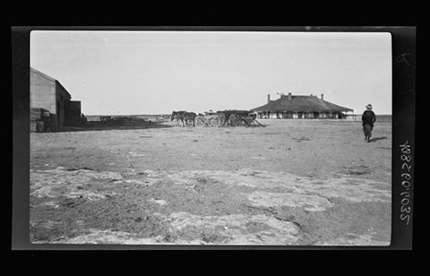 Nell Basedow (right) at Yalata station homestead, South Australia 1920. Two drays with horses are in the middle of the image. The corner of a large barn style building is at the left side of the image. The foreground shows bare earth with what appear to be exposed sections of flat rock.