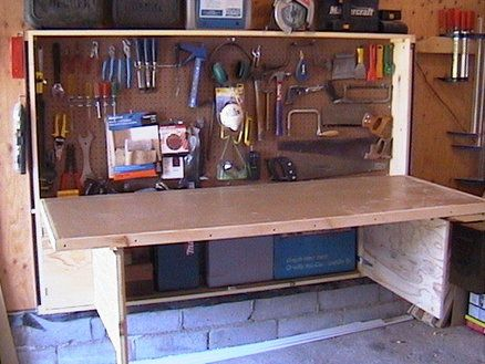 homemade foldaway pegboard and workbench, made from an old door