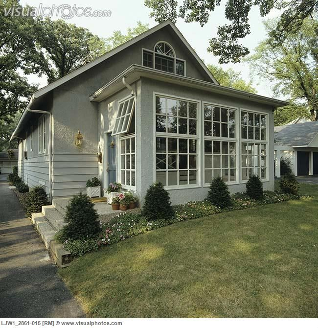 sunrooms front of small grey stucco bungalow addition of