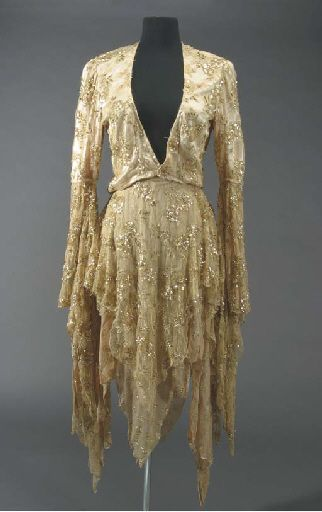"Stevie Nicks, Rhiannon Costume circa 1970s - A two-piece costume worn by Stevie Nicks during a performance of the song ""Rhiannon,"" written by Nicks about the mythological Welsh goddess Rhiannon - the Goddess of Steeds and the Maker of Birds. The costume consists of a short champagne and gold colored jacket with lace, sequins and applied gold thread with long flowing arms, together with a matching shawl that has a zipper on the left shoulder."