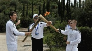 The first torch barrier Spyros Gianniotis, left, hands over the flame to British boxer Alexandros Lucas during the torch relay after the lighting ceremony in ancient Olympia, the sanctuary where the Olympic Games were born in 776 B.C.