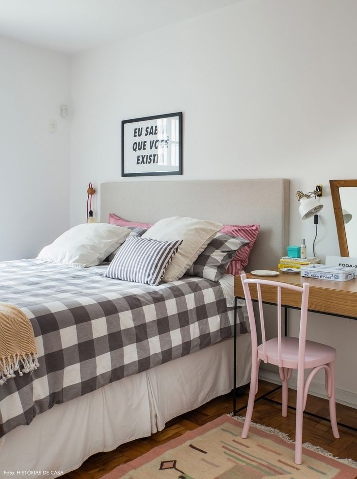 Quarto de casal tem roupa de cama xadrez, cabeceira revestida com tecido e penteadeira que também serve como criado mudo.