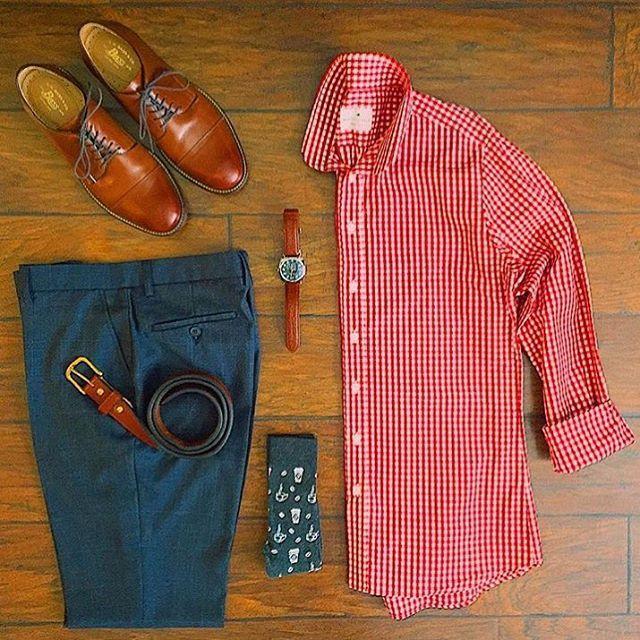 sapato Oxford marrom claro, calça azul em alfaiataria, cinto marrom claro, relógio com pulseira de couro marrom claro, camisa quadriculada vermelha e meia estampada.