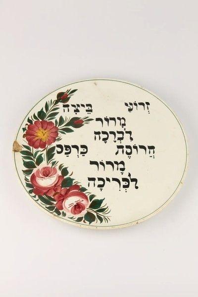 Misa sederová vyrobená z glazúrovanej keramiky.Pestrofarebná aplikácia  maľovaných florálnych vzorov vytvára polooválnu dekoráciu, hebrejské  nápisy korenín a rituálneho jedla, ktoré sa používajú na Pesach sú  maľované čiernou farbou. Glazúra i keramika sú lokálne poškodené na ľavom  okraji. Na zadnej strane značenie : CZECHOSLOVAKIA 443