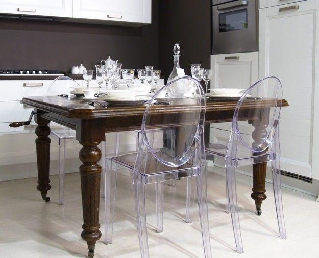 Sedie e tavolo dagli stili diversi - Tavolo antico in legno e moderne sedie in plexiglass per arredare la sala da pranzo.