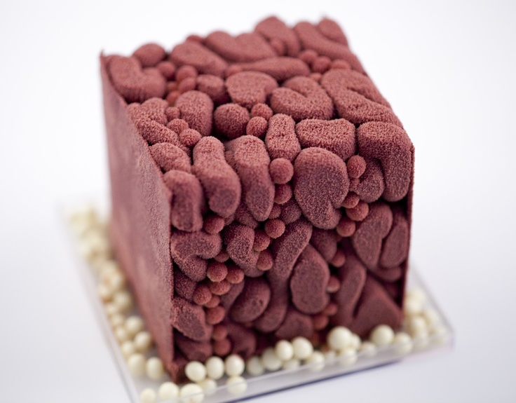 In this style, the ganache is piped into a disposable plastic cube when it is semi-crystallized, and various garnishes are added throughout, like puffed rice coated in chocolate, croquant, feuilletine, etc.