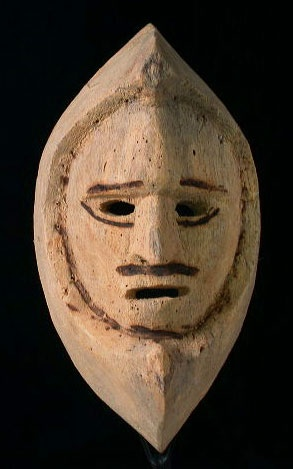 Native American shaman mask    Inuit people, Alaska    13 inches, wood    Images of some early masks collected in the Alaska area suggest that the interesting half-moon shape surrounding the face actually represents the jaws of an animal. Probably made out of driftwood, it is light weight and well scared with worm holes. The dark drawing was burned on, not painted.