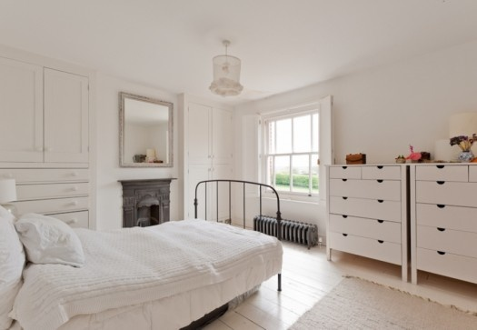 White bedroom with painted solid wooden shutters and built in wardrobes