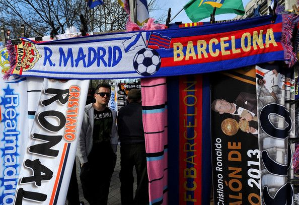 A fan looks at a stall dislaying merchandise of FC Barcelona and Real Madrid CF prior to the La Liga match between Real Madrid CF and FC Barcelona at estadio Santiago Bernabeu on March 23, 2014 in Madrid, Spain.