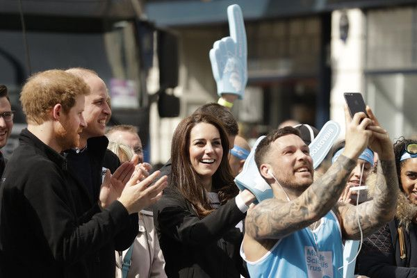 Kate Middleton Photos Photos - A runner stops to take a selfie backdropped by Britain's Prince Harry, Prince William, Duke of Cambridge and Catherine, Duchess of Cambridge cheering on runners at a Heads Together cheering point along the route of the 2017 London Marathon on April 23, 2017 in London, England. - The Duke