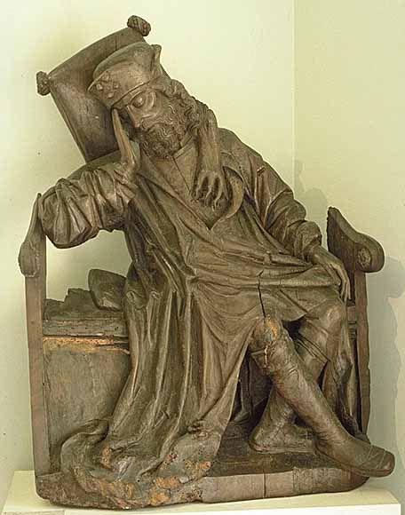 Pays-Bas début du XVIe siècle  Jessé  Fragment d'une représentation d'un arbre de Jessé  Noyer H. : 0,94 m. ; L. : 0,74 m. ; Pr. : 0,30 m.  De la poitrine de Jessé, le père du roi David, endormi sur son trône, jaillit l'arbre généalogique du Christ. Dans ce type de représentation, les branches de l'arbre portaient les ancêtres du Christ et au sommet apparaissaient la Vierge et l'Enfant.