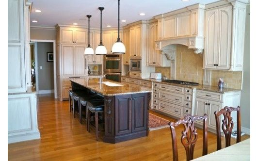 Traditional kitchen design with pendant lighting and island.