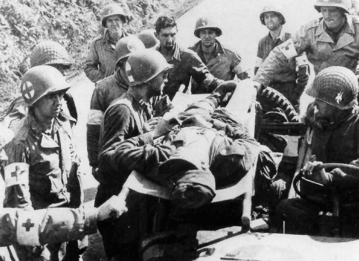 A young German soldier having just been treated by medical personnel of the 48th Armored Medical Battalion (2d Armd Div), is being prepared for evacuation to the rear. Picture taken during 'Operation Cobra', Normandy, France, July 28, 1944.