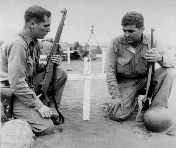 Raritan, New Jersey's Tony Cirello and another soldier pay their respects at John Basilone's grave at Iwo Jima in this 1945 photo.  After the war, the bodies of the fallen soldiers at Iwo Jima would be returned to the U.S.
