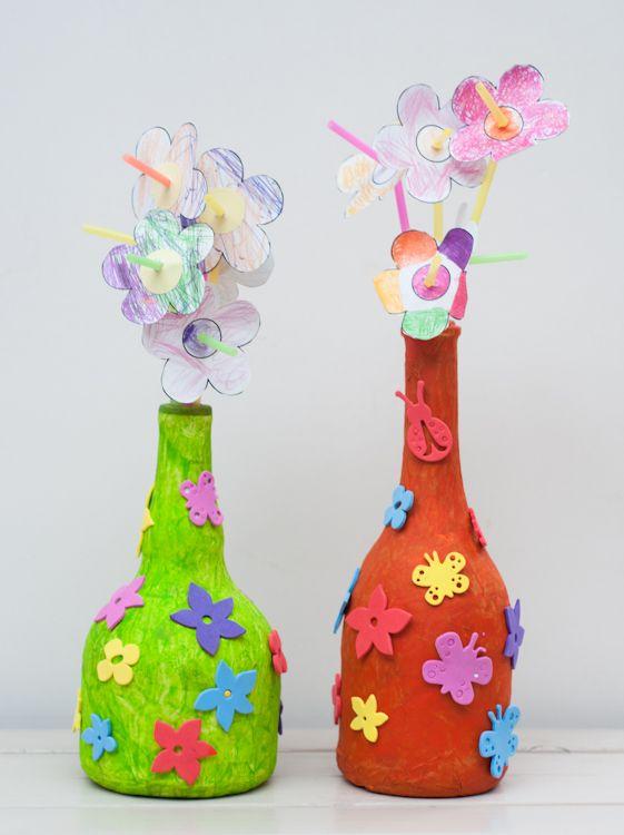 Een vaas voor mama: fles beplakken met een laag papier-maché, daarna nog een laag papier-maché gemengd met verf. Versieren met foam-figuurtjes. Bloemen inkleuren, uitknippen en aan een rietje bevestigen.