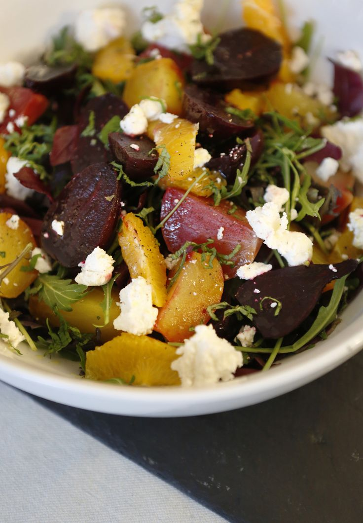 A salad of multi colored beetroot, soft goat's cheese and orange