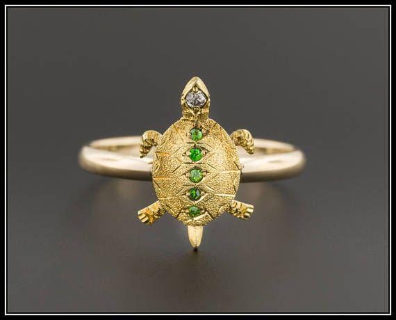 Een demantoid garnet & diamant schildpad ring gemaakt van een antieke stick pin (circa 1900-1910).  Deze ring is voorzien van een fijn gedetailleerde 14 karaats vergulde schildpad geaccentueerd met een rij van demantoid granaten en een diamant in zijn hoofd. Onze juwelier de schildpad uit de pin van de stok verwijderd en gelast het op een 10 k gouden band maken deze ring.  De ring is in zeer goede staat; echter nog de hoogste demantoid garnet veilig, gechipt (zichtbaar alleen onder vergro...