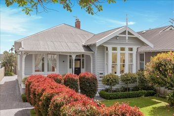 Exterior of home with pretty stained glass windows. 3 bedroom wooden villa @ Herbert Rd, Mt Eden. (For sale @ 2 million NZD, Nov 2012.)