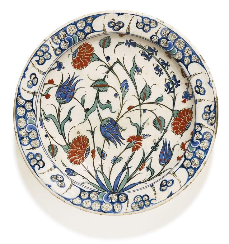 AN IZNIK POLYCHROME POTTERY DISH WITH FLORAL STEMS, TURKEY, CIRCA 1580 decorated in underglaze cobalt blue, viridian green and relief red with black outlines, with a leafy tuft issuing floral sprays, including three large carnations, tulips, hyacinths and prunus branches, the rim with breaking wave pattern, floral details to exterior, old collection label to underside and single red bole dot in the centre 31cm. diam. Sotheby's