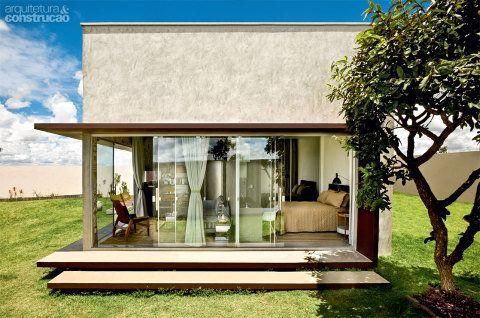 Sete portas deslizantes formam uma cortina de 8,85 m de vidro temperado nas fachadas sudeste e sudoeste, dissolvendo a fronteira entre o interior e o gramado. Quando abertas, permitem que as festas do morador se estendam da casa ao jardim. Projeto de Eduardo Sáinz.
