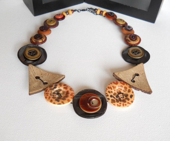 This gorgeous button necklace is a beautiful and unique statement piece of jewellery and features some absolutely stunning buttons making it striking!  Featuring an array of beautiful wooden, brown and antique gold coloured metal buttons, complimented by 2 leopard print wooden buttons, this arrangement of buttons truly unique. It has been hand crafted along black coloured vinyl covered wire, making it easy to flex and mold around your neck with comfort. Please note some buttons may feature…